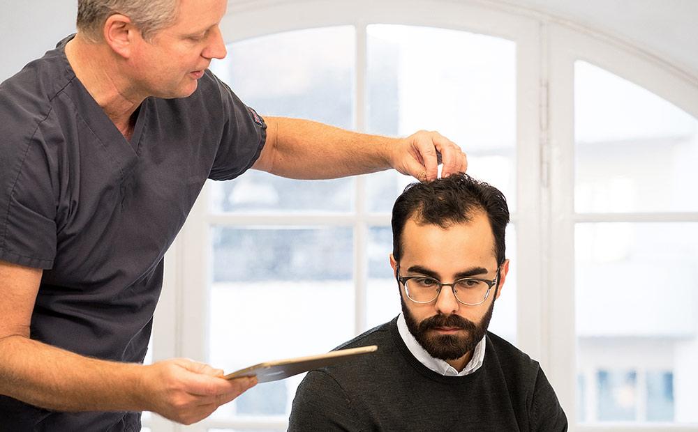En man som får sitt hår undersökt under en konsultation inför en hårtransplantation.