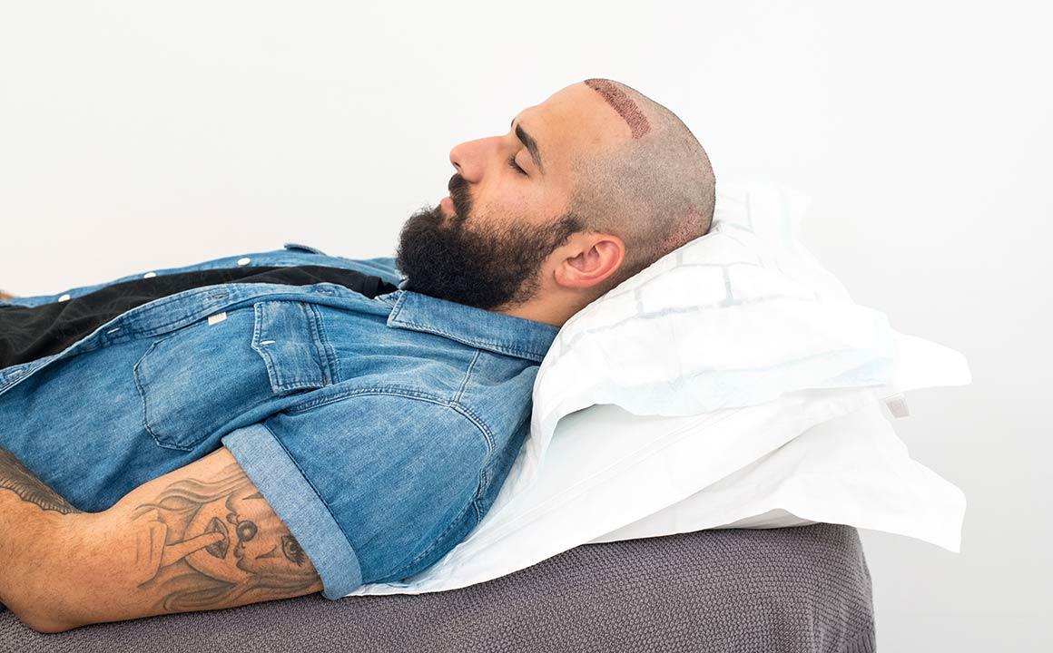 En man sover med uppstaplade kuddar.